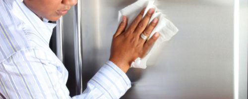 Woman cleaning her stainless steel refrigerator with a cloth